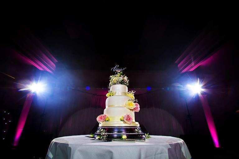 Wedding cake lit up on dance floor at Surrey wedding