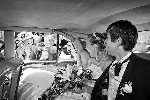 Bride and groom wave to guests from wedding car as they leave church for wedding venue Surrey
