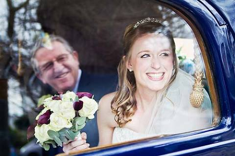 Bride smiling at her dad from wedding car on wedding day in Surrey