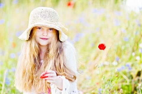 Child outdoor photo session among wild flowers
