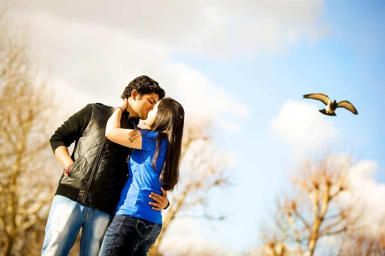 Engaged couple kissing in park with pigeon flying overhead on pre wedding photo shoot in London