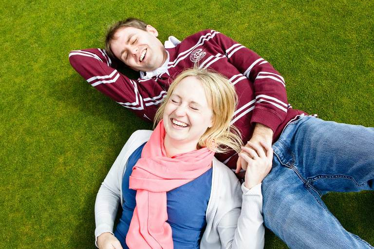 Young couple laying on grass laughing together during their pre wedding photo shoot in Kent