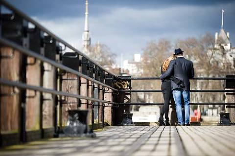 Engaged couple holding each other and looking over the Thames in London