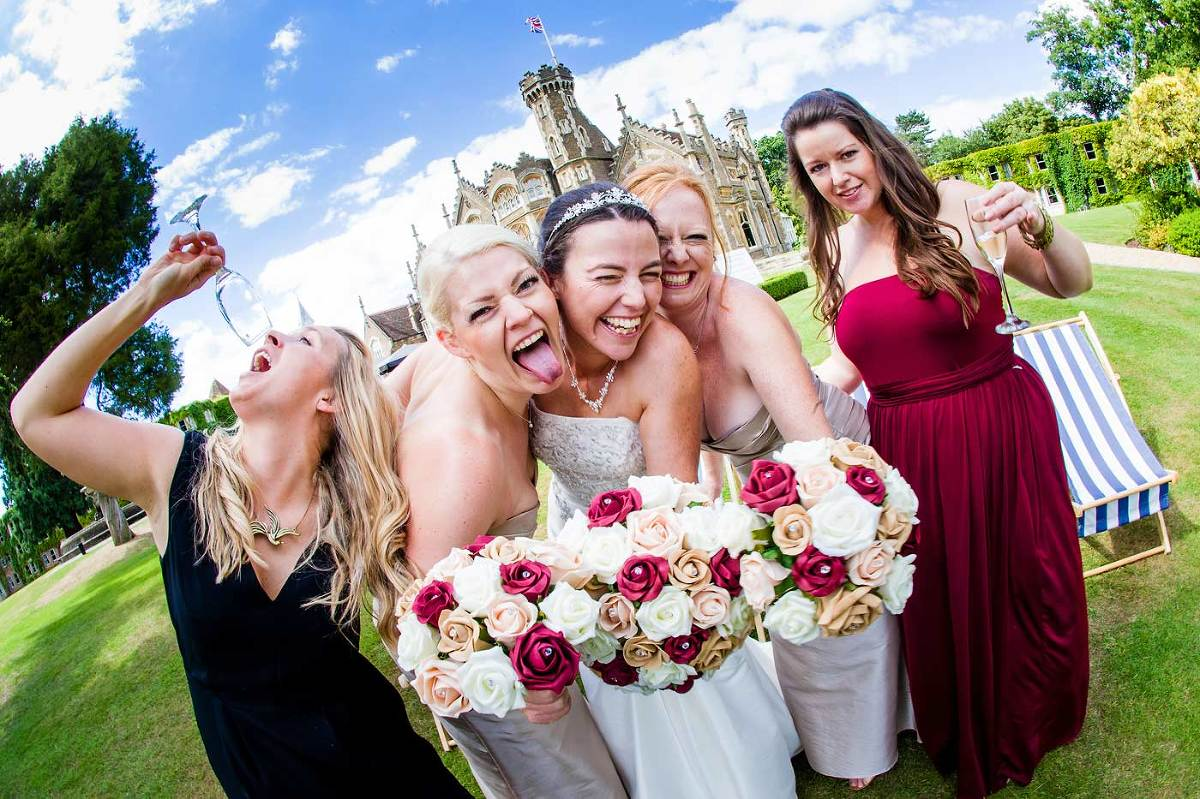 Bride and bridesmaids fun shot on wedding day at Oakley Court Windsor