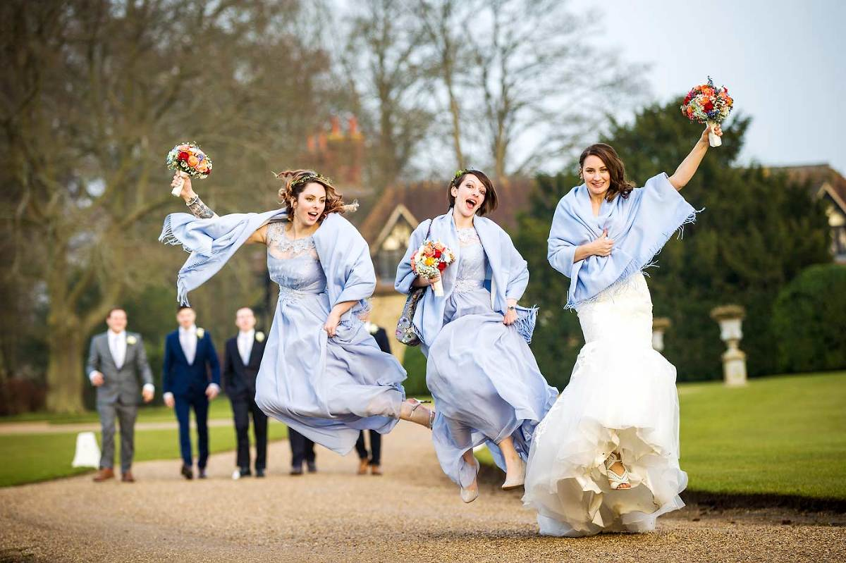 Bride and bridesmaids jumping on wedding day at Loseley Park Surrey